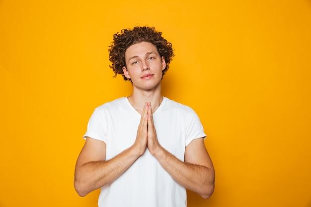 Retrato de um homem de cabelos cacheados sorridente rezando