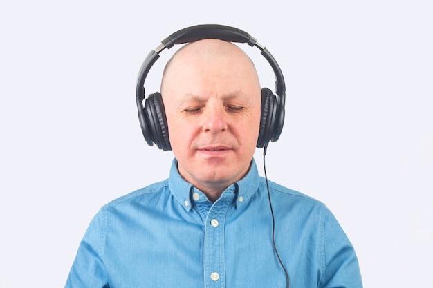 Retrato de um homem de camisa azul com fones de ouvido relaxando e ouvindo música