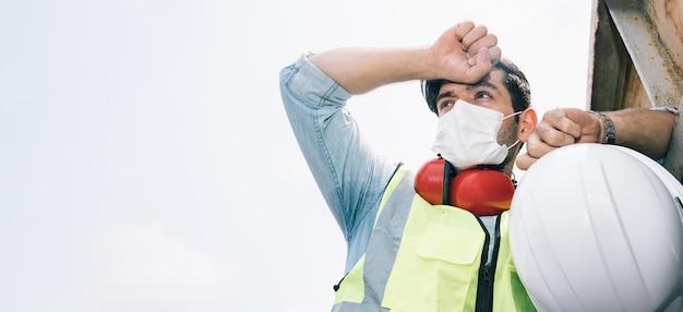 Retrato de um homem de engenharia bonito com capacete de segurança descansando