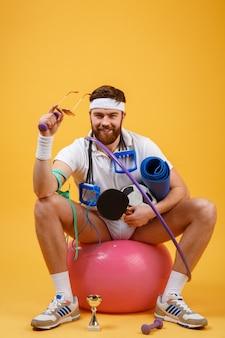 Retrato de um homem de esportes, sentado em uma bola de fitness