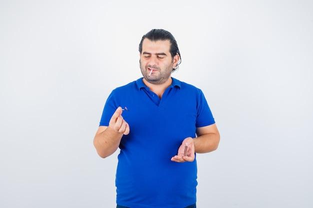 Retrato de um homem de meia-idade acendendo fósforos com uma camiseta polo e olhando pensativo para a frente