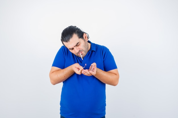 Retrato de um homem de meia-idade acendendo um cigarro com fósforos em uma camiseta polo e olhando de frente para o foco
