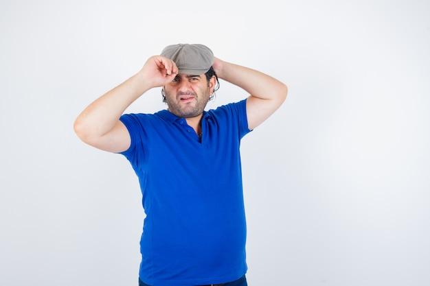 Retrato de um homem de meia-idade ajustando o boné em uma camiseta polo, chapéu de hera e parecendo indeciso com a vista frontal