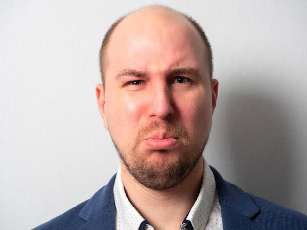 Retrato de um homem de meia-idade de terno. uma expressão ofendida. emoções. ele desenrolou o lábio inferior Foto Premium