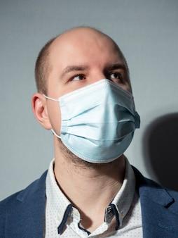 Retrato de um homem de meia-idade em um terno e máscara médica, olhando para longe.