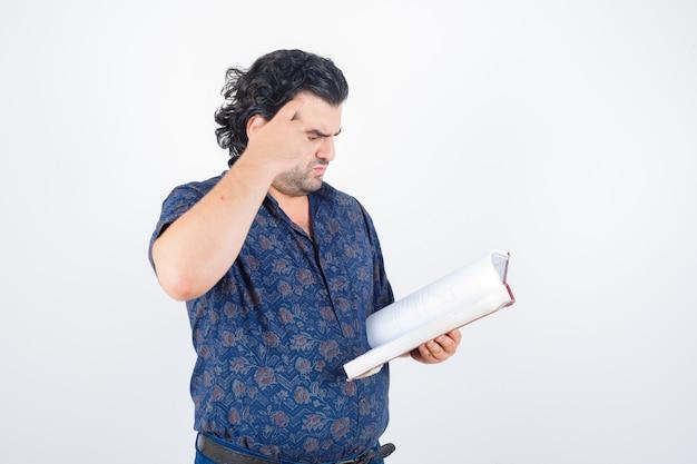 Retrato de um homem de meia-idade olhando um livro em uma camisa e olhando de frente com atenção