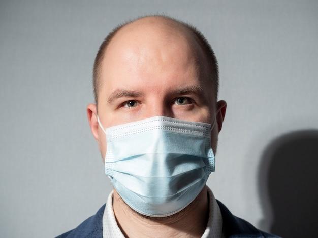 Retrato de um homem de meia-idade vestido com uma máscara médica e terno. olha para a câmera