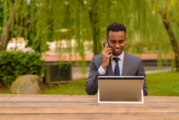 Retrato de um homem de negócios africano bonito ao ar livre vestindo terno