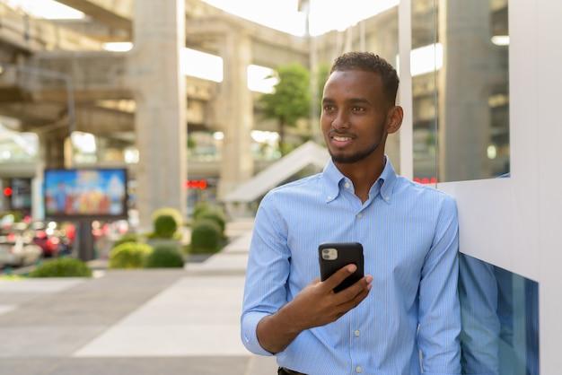 Retrato de um homem de negócios africano negro bonito ao ar livre na cidade durante o verão, usando telefone celular, sorrindo e pensando