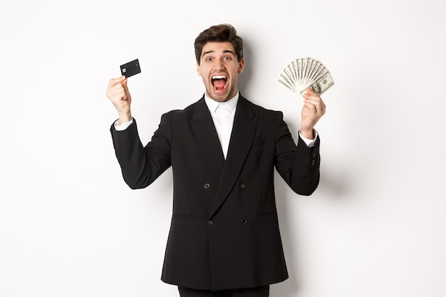 Retrato de um homem de negócios bonito em terno preto, mostrando cartão de crédito e dinheiro, gritando de alegria e emoção, em pé contra um fundo branco