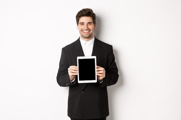 Retrato de um homem de negócios bonito em um terno da moda, mostrando a tela do tablet digital e sorrindo, em pé contra um fundo branco