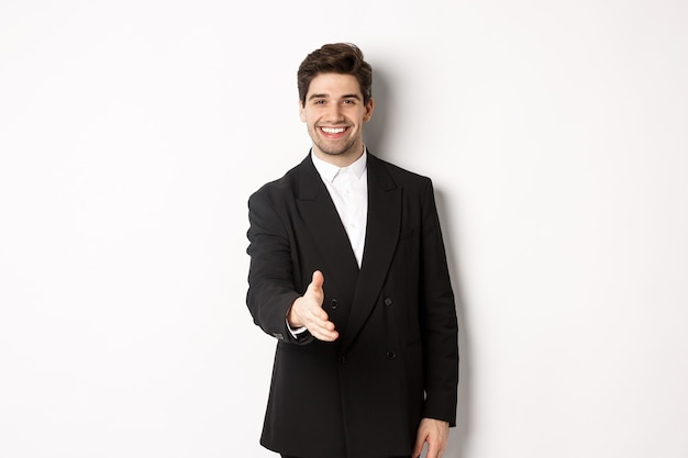 Retrato de um homem de negócios bonito em um terno preto, estendendo a mão para um aperto de mão, cumprimentando os parceiros de negócios e sorrindo, bem-vindo à empresa, em pé sobre um fundo branco