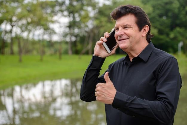 Retrato de um homem de negócios bonito maduro feliz falando ao telefone no parque