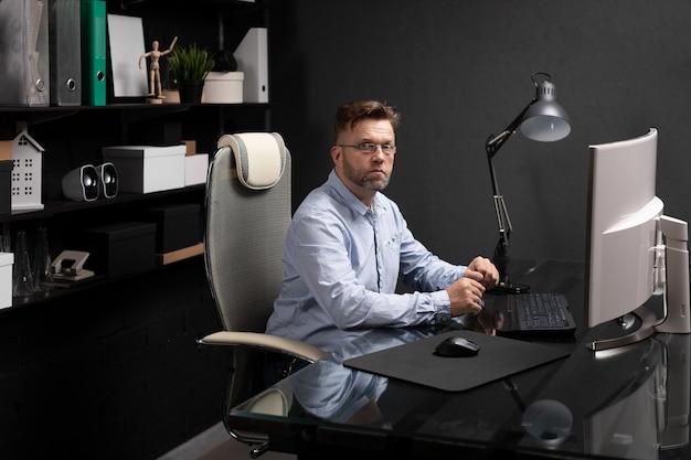 Retrato de um homem de negócios com óculos sentado no escritório em frente ao computador