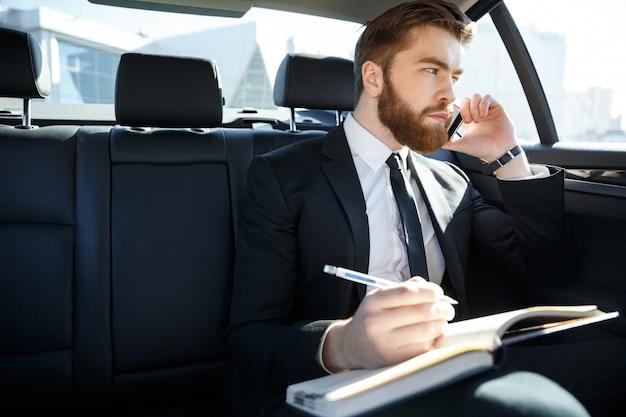 Retrato de um homem de negócios com papéis chamando em smartphone