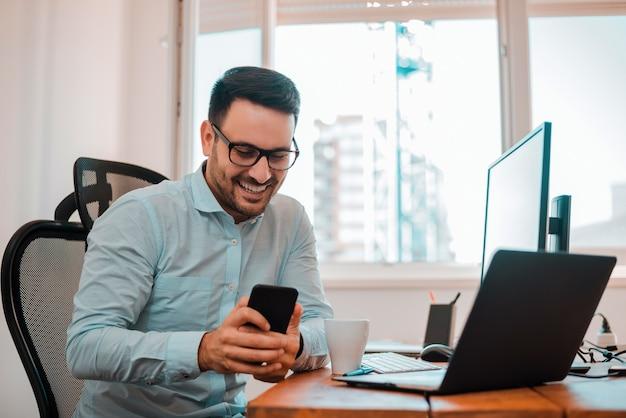Retrato de um homem de negócios de sorriso feliz nos monóculos usando o smartphone ao sentar-se no escritório.