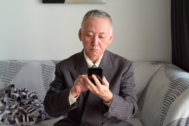 Retrato de um homem de negócios japonês maduro em casa em quarentena devido à pandemia do vírus corona covid-19