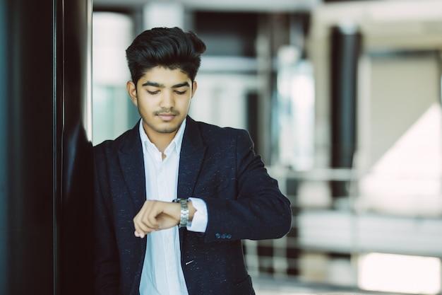 Retrato de um homem de negócios jovem assistindo relógio no escritório