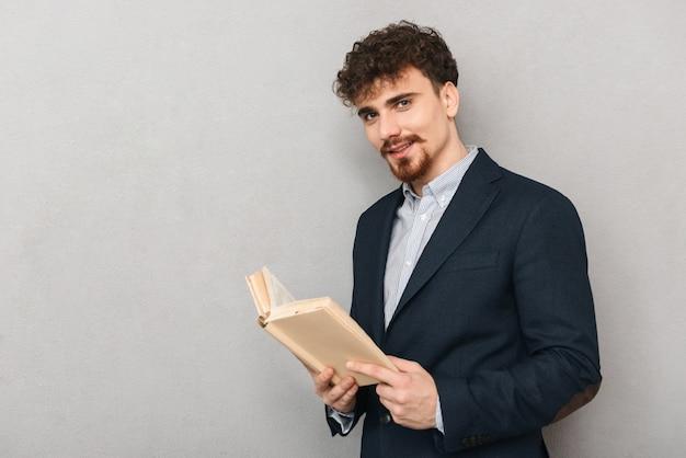 Retrato de um homem de negócios jovem bonito isolado sobre o livro de leitura de parede cinza.