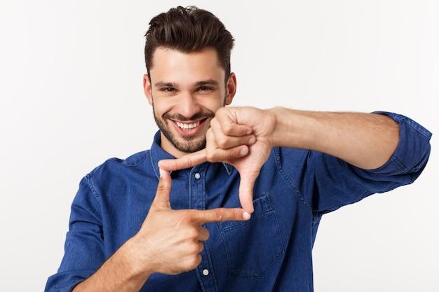 Retrato de um homem de negócios jovem fazendo uma moldura com os dedos e sorrindo, em branco.