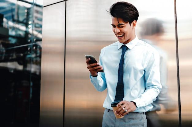 Retrato de um homem de negócios novo feliz using mobile phone na cidade urbana. estilo de vida das pessoas modernas. de pé junto à parede com uma xícara de café