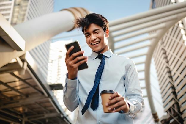 Retrato de um homem de negócios novo feliz using mobile phone na cidade urbana.