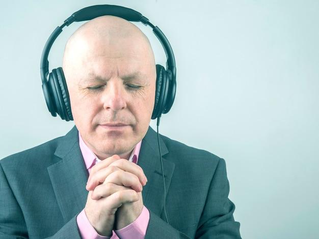Retrato de um homem de negócios relaxando com fones de ouvido e ouvindo sua música favorita