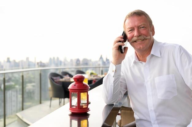 Retrato de um homem de negócios sênior bonito com bigode em um restaurante na cobertura