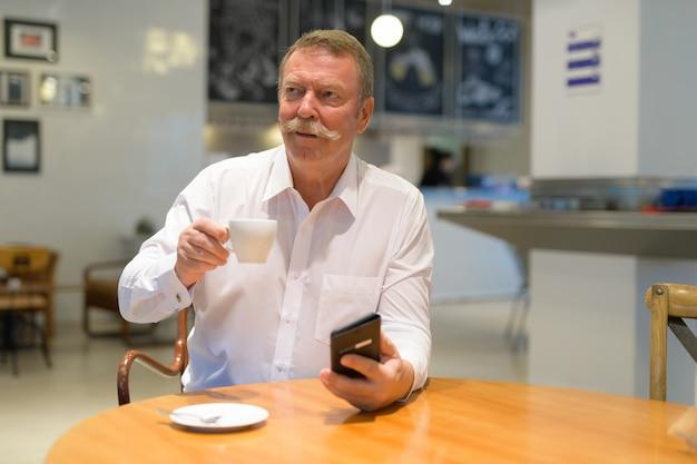 Retrato de um homem de negócios sênior bonito com bigode na cafeteria