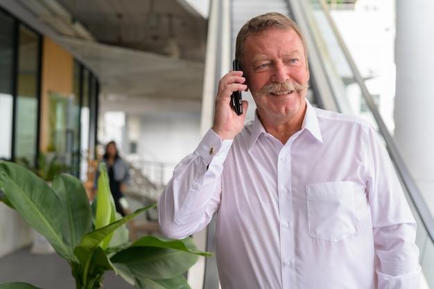 Retrato de um homem de negócios sênior bonito com bigode na cidade