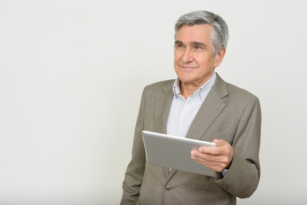 Retrato de um homem de negócios sênior bonito e feliz pensando enquanto usa o tablet digital