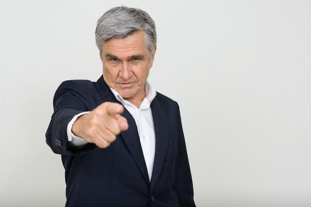 Retrato de um homem de negócios sênior bonito em um terno apontando para a câmera