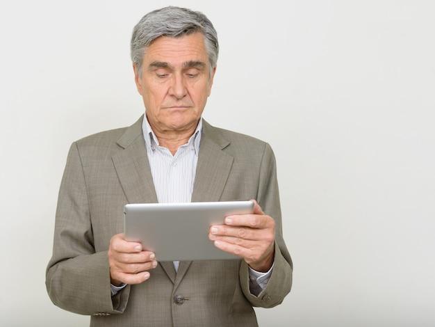 Retrato de um homem de negócios sênior bonito usando tablet digital
