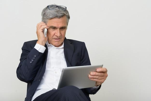 Retrato de um homem de negócios sênior bonito usando telefone e tablet digital