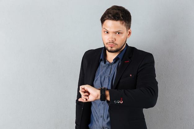Retrato de um homem de negócios sério, verificando o tempo