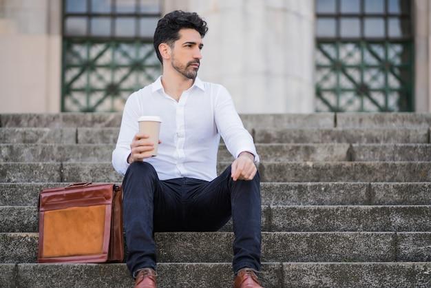 Retrato de um homem de negócios tomando uma xícara de café no intervalo do trabalho enquanto está sentado na escada ao ar livre
