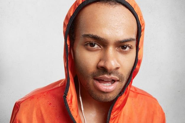 Retrato de um homem de pele escura e úmido ouve música, usa um casaco com capuz e caminha em um dia chuvoso