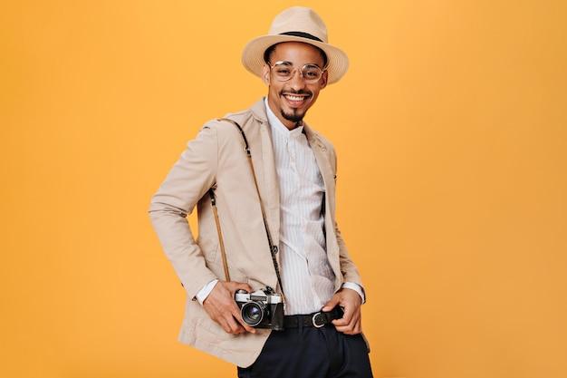 Retrato de um homem de terno bege segurando uma câmera retro na parede laranja