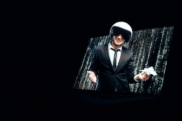 Retrato de um homem de terno e capacete. ele lança um avião de papel a partir de uma tela de laptop.