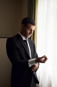Retrato de um homem de terno e gravata perto da janela. o noivo está se preparando para a cerimônia de casamento