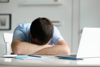 Retrato de um homem deitado na mesa perto do laptop