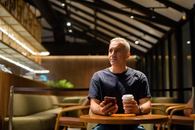 Retrato de um homem dentro da cafeteria à noite pensando e usando o telefone celular
