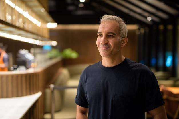 Retrato de um homem dentro da cafeteria à noite, sorrindo e pensando, foto horizontal
