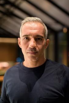 Retrato de um homem dentro da cafeteria à noite.