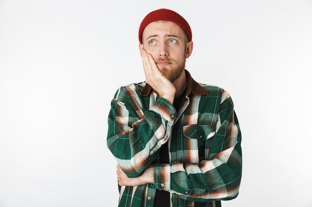 Retrato de um homem descontente usando chapéu e camisa xadrez, segurando seu rosto, em pé, isolado sobre um fundo branco