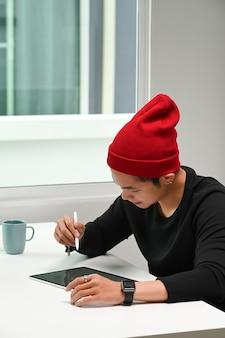 Retrato de um homem designer gráfico com chapéu de lã vermelha usando a mesa gráfica em seu espaço de trabalho