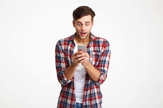 Retrato de um homem divertido e feliz, olhando para o telefone móvel