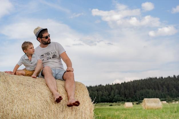 Retrato de um homem e seu filho sentado em um palheiro redondo em um campo verde em um dia ensolarado de verão