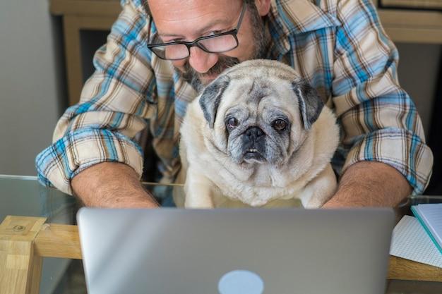 Retrato de um homem e um cachorro trabalhando juntos em casa com o conceito de computador laptop de estilo de vida de trabalho inteligente grátis pessoas caucasianos digitando no teclado na estação de trabalho moderno trabalho online digital