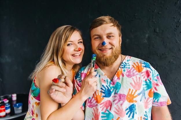 Retrato de um homem e uma mulher sorrindo, com um pincel nas mãos e narizes pintados. uma família alegre passa tempo juntos, aprendendo a desenhar.